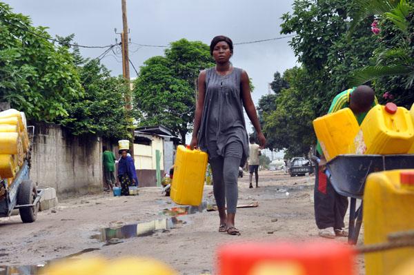 Devant un forage, une jeune fille s'approche pour acheter de l'eau