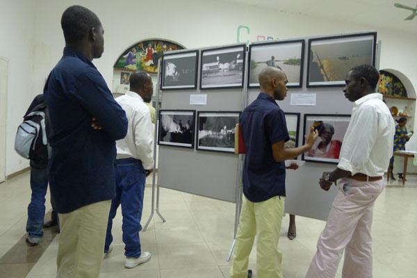 Arnaud MAKALOU (à droite) en discussion devant ses photos